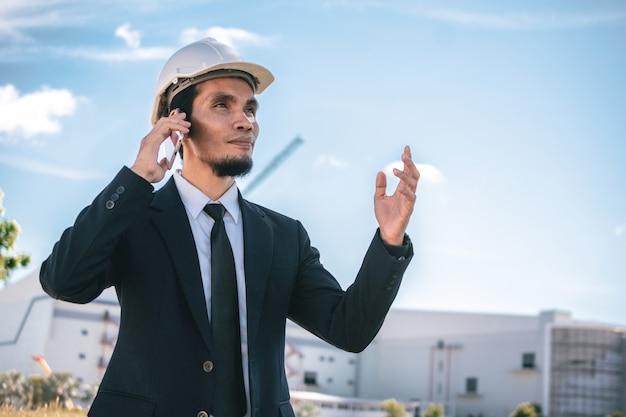 Geschäftsmann anruf telefon im freien vor ort bau arbeiten