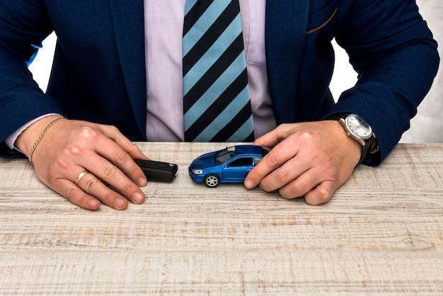 Geschäftsmann arbeitet am bürospielzeugauto und schlüsselverkauf oder mietautokonzept