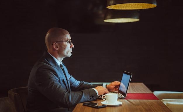 Geschäftsmann arbeitet am computer im geschäftszentrum. seitenansicht des selbstbewussten kaukasischen mannes verwendet laptop
