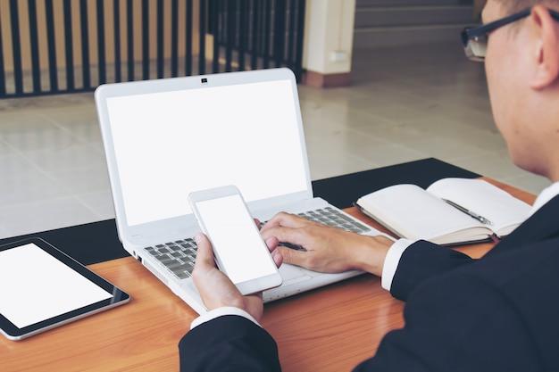 Geschäftsmann arbeitet an laptop und smartphone.