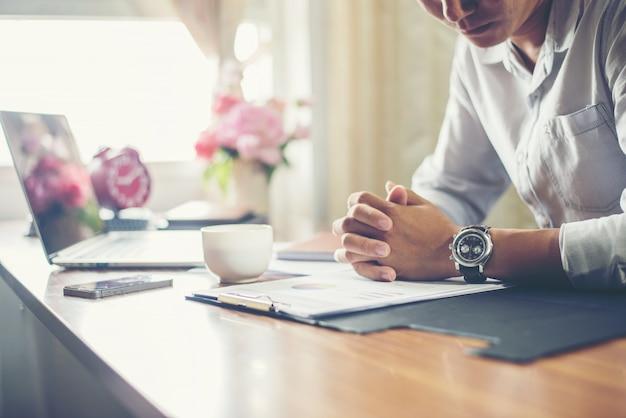 Geschäftsmann arbeitet an seinem schreibtisch mit einer tasse kaffee im büro.
