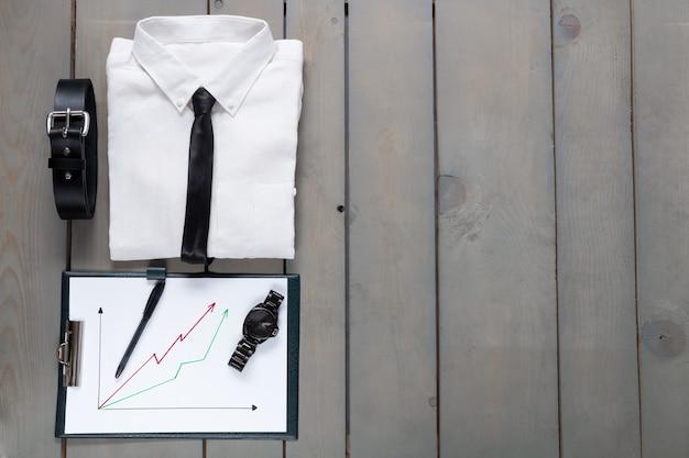 Geschäftsmann, arbeitsausstattung auf grauem hölzernem hintergrund. weißes hemd mit schwarzer krawatte, gürtel, planchette. zurück an die arbeit.