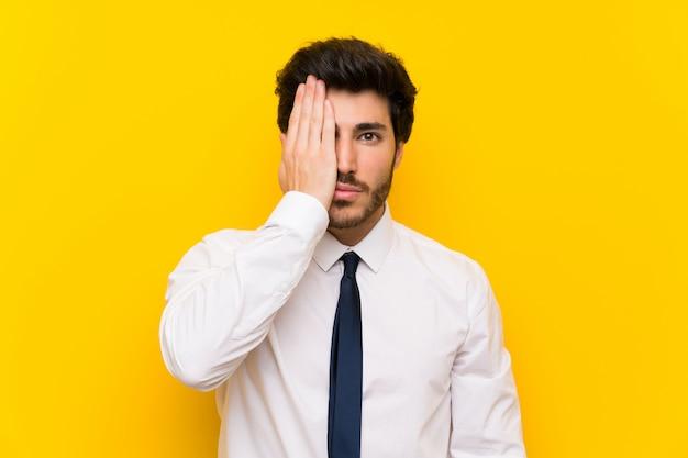 Geschäftsmann auf dem lokalisierten gelb, das eigenhändig ein auge bedeckt