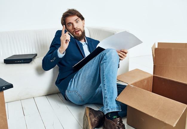 Geschäftsmann auf der couch mit kisten, die neue arbeitsorte transportieren