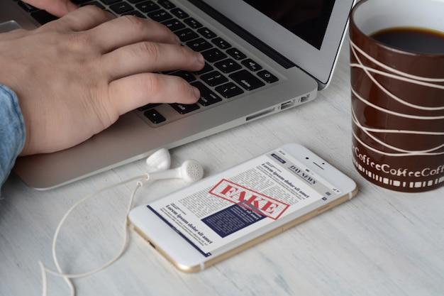 Geschäftsmann auf der tastatur mit tasse kaffee und digitalen gefälschten nachrichten auf smartphone