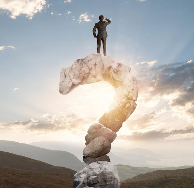 Geschäftsmann auf einem berg geformt wie ein fragezeichen
