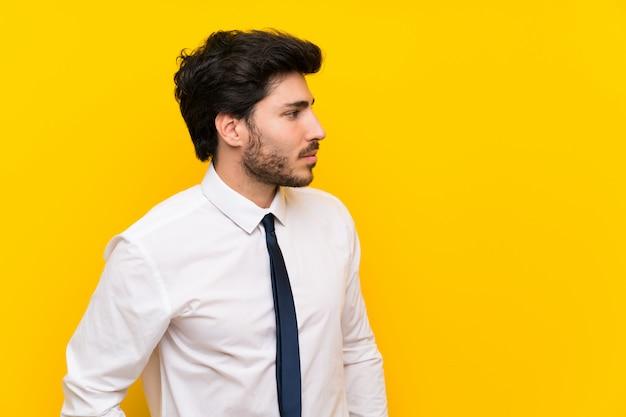 Geschäftsmann auf lokalisiertem gelbem hintergrund, der seite steht und schaut