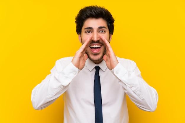 Geschäftsmann auf lokalisierter gelber wand schreiend mit dem breiten mund öffnen sich