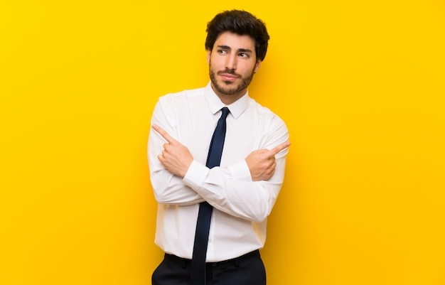 Geschäftsmann auf lokalisierter gelber wand zeigend auf die seitenteile, die zweifel haben