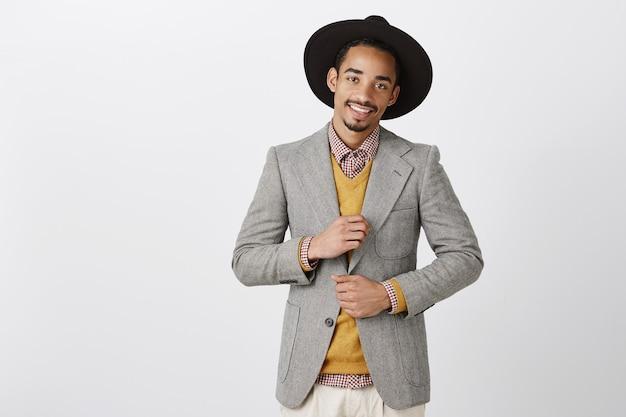 Geschäftsmann auf party, erfolgreiches geschäft feierend. selbstbewusster charmanter afroamerikanischer unternehmer in stilvoller formeller kleidung und hut, der das outfit überprüft und breit lächelt, frech über der grauen wand