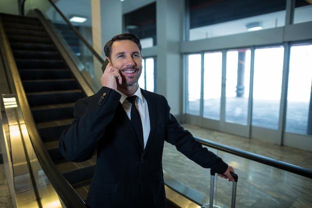 Geschäftsmann auf rolltreppe, die auf handy spricht
