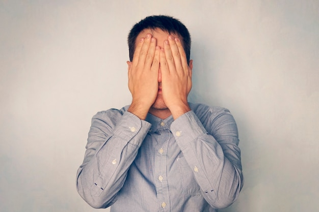 Geschäftsmann bedeckt sein gesicht mit den händen. müdigkeit und stress bei der arbeit. der junge mann bedeckte seine augen mit den händen. hör auf zu sehen. gesicht ausblenden. Premium Fotos