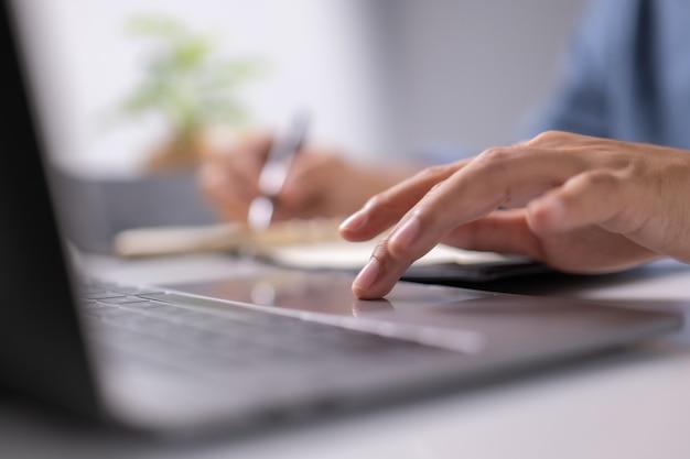 Geschäftsmann bedienen den tisch, der den hintergrund des datenbüroschreibtischs überprüft und eine notiz auf dem tisch schreibt