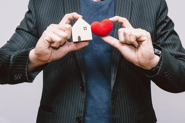 Geschäftsmann behandeln haus und rotes herz für zu hause bleiben oder lieben pflegeleute im hausfamilienkonzept.