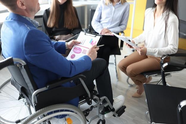 Geschäftsmann behinderter trainer im rollstuhl, der mit menschen nahaufnahme diskutiert