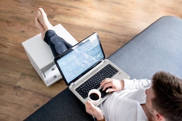 Geschäftsmann bei der arbeit. ansicht des mannes, der am laptop beim sitzen an der couch arbeitet