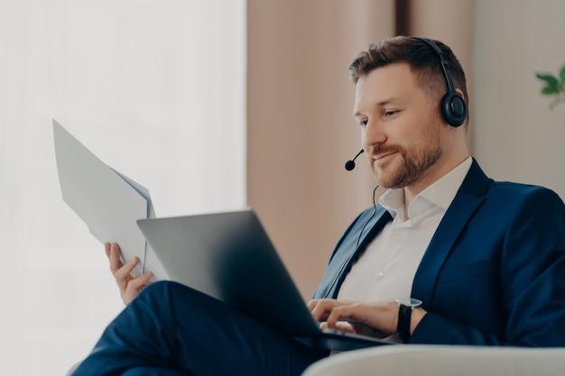 Geschäftsmann bei der arbeit. lächelnder bärtiger männlicher chef, der dokumente und laptop auf seinem schoß hält, während er drinnen sitzt und ein online-meeting hat. geschäftsleute und moderne technologien