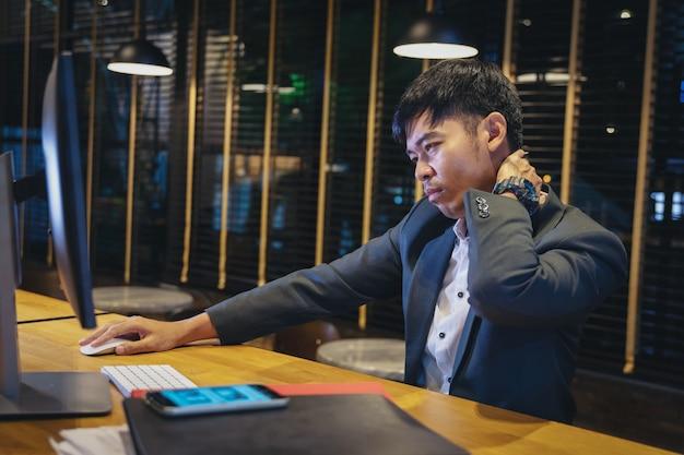 Geschäftsmann bei der arbeit leiden unter nackenschmerzen