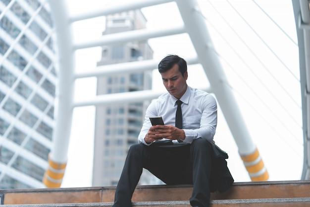Geschäftsmann benutzt das mobiltelefon, das im freien sitzt