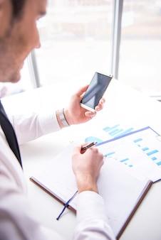 Geschäftsmann benutzt handy am schreibtisch im büro.