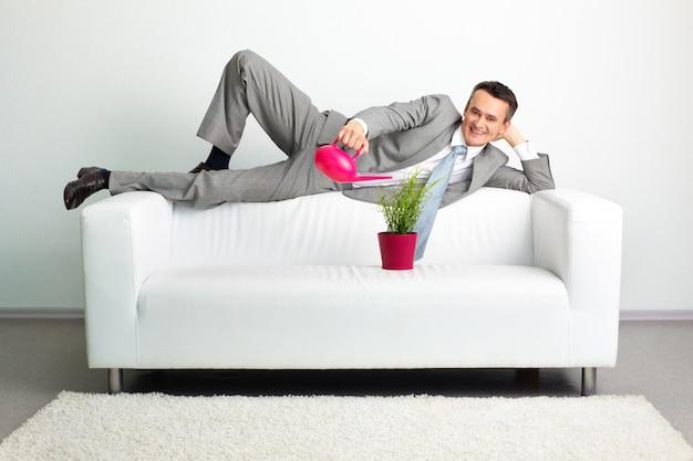 Geschäftsmann bewässerung einer pflanze