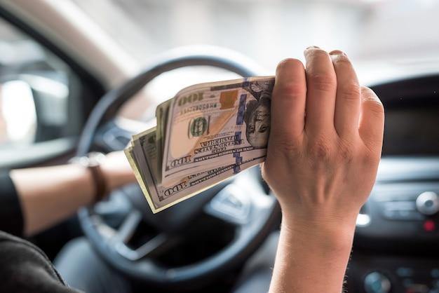 Geschäftsmann bezahlt für ein produkt oder eine dienstleistung, gibt dollars, während er im auto sitzt. finanzkonzept