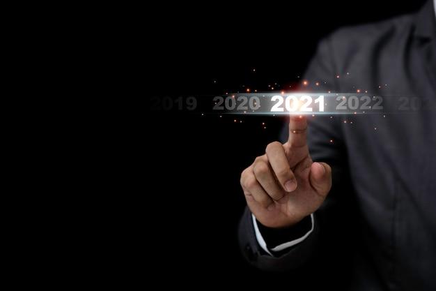 Geschäftsmann, der 2021 jahre berührt, um neues jahr und neues unternehmensgründungskonzept zu beginnen.