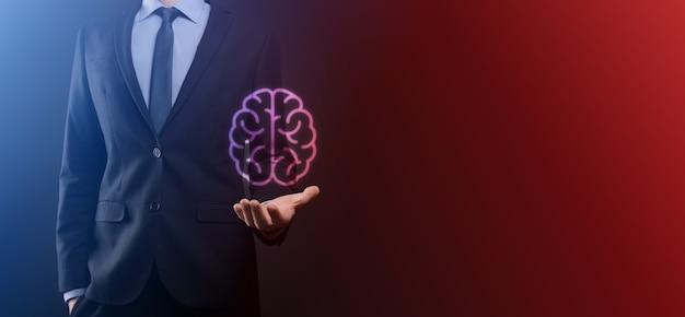 Geschäftsmann, der abstrakte gehirn- und symbolwerkzeuge, gerät, kundennetzwerkverbindungskommunikation auf virtueller, innovativer entwicklung, zukunftstechnologie, wissenschaft, innovation und geschäftskonzept hält.