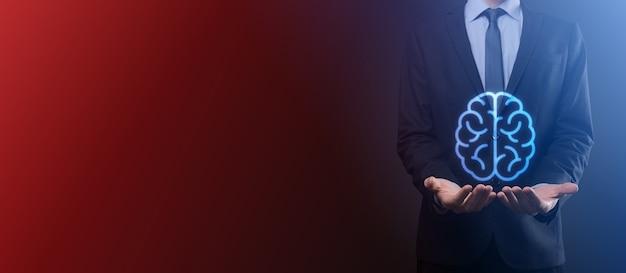 Geschäftsmann, der abstrakte gehirn- und symbolwerkzeuge, geräte-, kundennetzwerkverbindungskommunikation auf virtueller, innovativer entwicklungszukunftstechnologie, wissenschaft, innovation und geschäftskonzept hält.