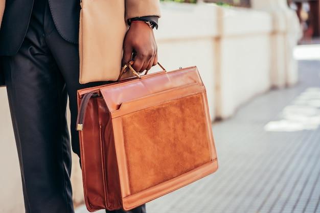 Geschäftsmann, der aktentasche beim gehen zur arbeit im freien hält. unternehmenskonzept.