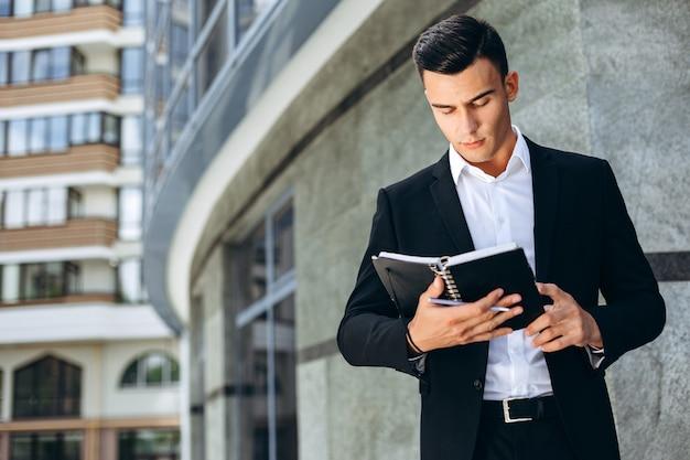 Geschäftsmann, der als nächstes ein geschäftsgebäude hält einen papierplaner und schaut in ihm steht - bild