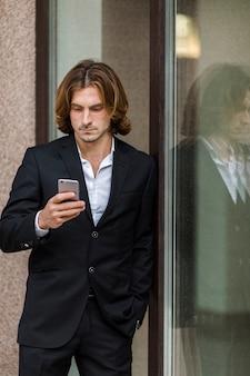 Geschäftsmann, der am fenster sein telefon überprüft