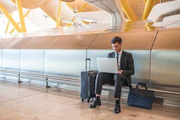 Geschäftsmann, der am flughafen mit dem laptop lächelt arbeitet, auf seinen flug mit gepäck wartend