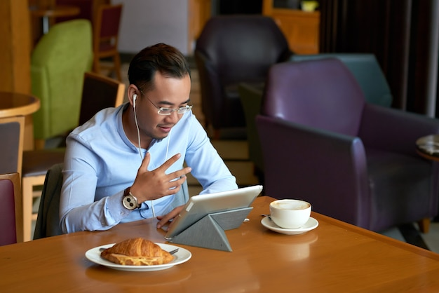 Geschäftsmann, der am frühstück im café videocalling ist