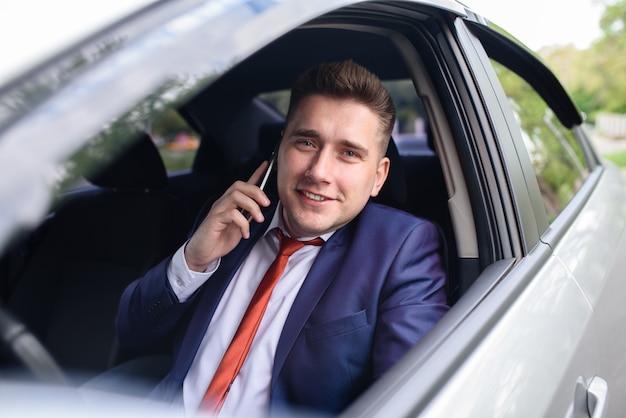 Geschäftsmann, der am handy im auto spricht.