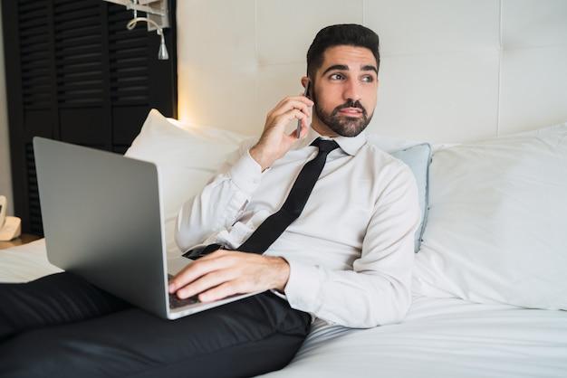 Geschäftsmann, der am hotelzimmer am telefon spricht