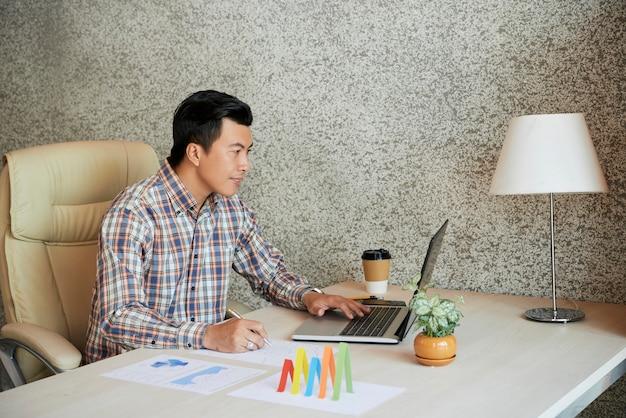 Geschäftsmann, der am laptop arbeitet