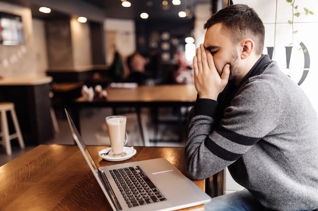 Geschäftsmann, der am laptop mit kopfschmerz im cafégeschäft an der terrasse arbeitet.
