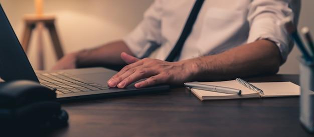 Geschäftsmann, der am laptop mit notiz auf buch im büro in der nacht arbeitet.