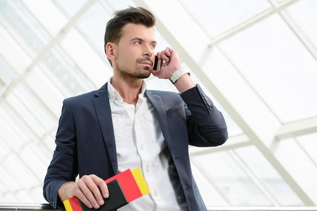 Geschäftsmann, der am reisenden gehen des telefons spricht.