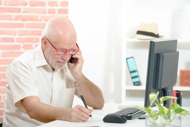 Geschäftsmann, der am schreibtisch sitzt und auf mobiltelefon spricht