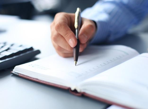 Geschäftsmann, der am schreibtisch sitzt und einen vertrag mit flachem fokus auf unterschrift unterzeichnet.