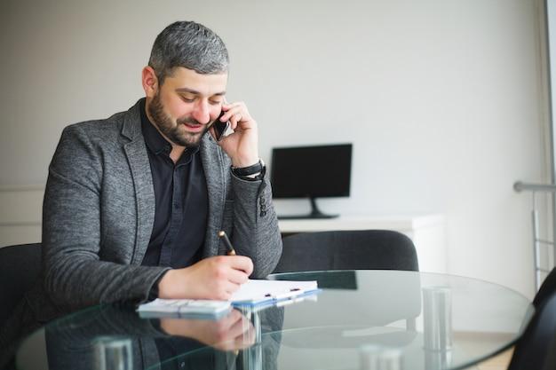 Geschäftsmann, der am schreibtisch sitzt und vertrag unterzeichnet.