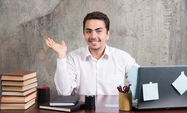 Geschäftsmann, der am schreibtisch sitzt, während er lächelt.