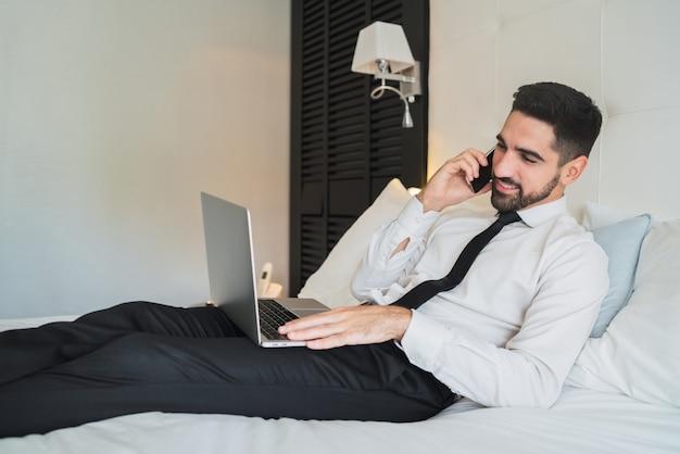 Geschäftsmann, der am telefon am hotelzimmer spricht.