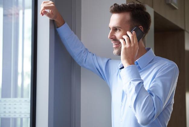 Geschäftsmann, der am telefon bei der arbeit spricht