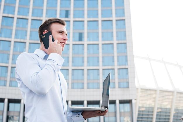 Geschäftsmann, der am telefon beim halten des laptops spricht