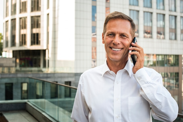 Geschäftsmann, der am telefon betrachtet kamera spricht