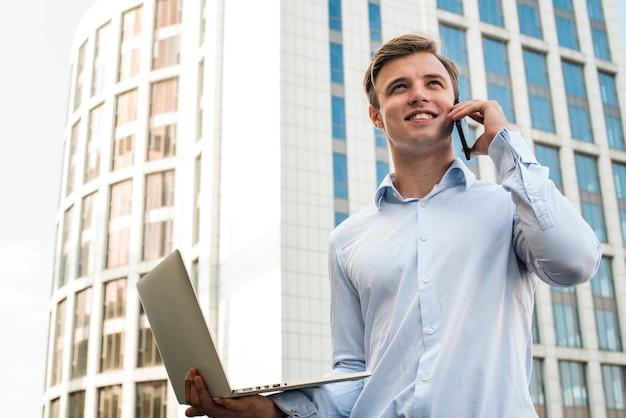 Geschäftsmann, der am telefon hält laptop spricht