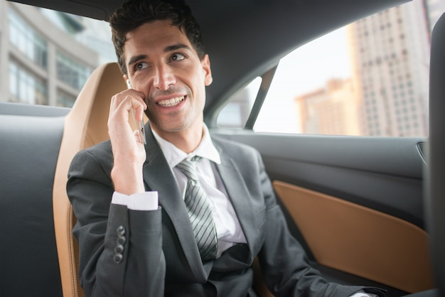 Geschäftsmann, der am telefon im auto spricht